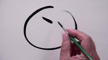 mão humana desenhando um smiley infeliz com tinta preta