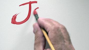 """Mano humana escribiendo la palabra """"joyeux noel"""" en francés, con gouache rojo"""