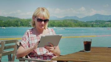 Technology on vacation. Woman with tablet sitting at a table in a cafe in front of the lake and mountains. Resort in Spain