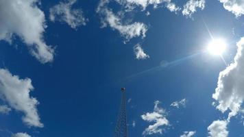 Wolken und blauer Himmel vergehen in der Nähe des Kommunikationsturms