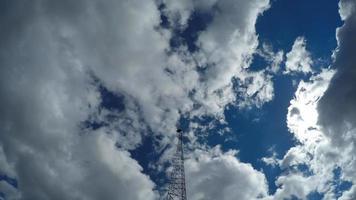 flauschiger weißer Wolkenzeitraffer mit Mikrowellenturm im Vordergrund