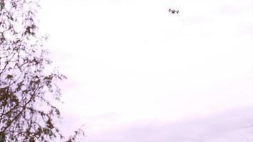 un petit drone volant au-dessus des maisons et des arbres à l'extérieur