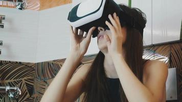 Young girl sitting in bathroom in virtual reality glasses on head. Looking up