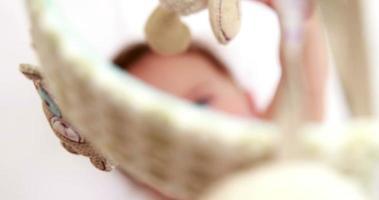 bébé jouant avec un mobile dans son berceau