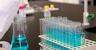 jovem cientista usando pipeta para colocar produto químico em tubo de ensaio
