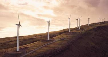 Luftaufnahme von Windmühlen, die sich bei Sonnenuntergang drehen