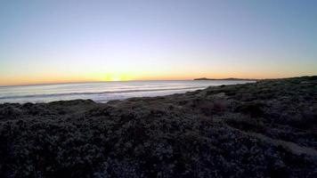 Visão aérea estabilizada de 4k da câmera voando sobre os arbustos da praia até a praia de areia branca enquanto um adolescente caminha na praia e a câmera se levanta para ver o pôr do sol sobre o oceano pacífico no norte da Califórnia
