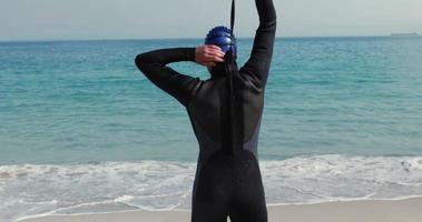 Rückansicht des Schwimmers, der sich am Strand fertig macht
