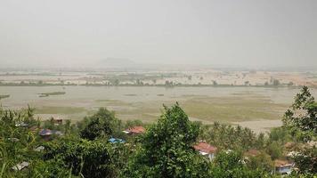 pequena cidade rural entre vegetação tropical e arrozais inundados ao fundo