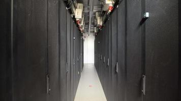 uma longa série de gabinetes especiais projetados para servidores de ventilação em uma grande planta industrial. dispositivos conectados a uma fonte de alimentação comum por cabos com plugue vermelho. corredor estreito com lâmpada para iluminação video