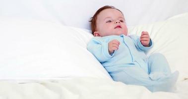 neonato in babygro blu sdraiato sui cuscini