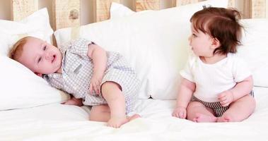 lindos bebés en una cama