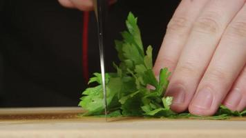 CLOSE UP: A cook cuts a parsley on a cutting board in a kitchen