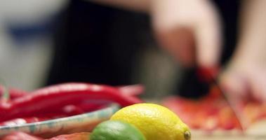 einen roten Pfeffer hacken. flacher Fokus. Zitrone und Limette im Fokus. video