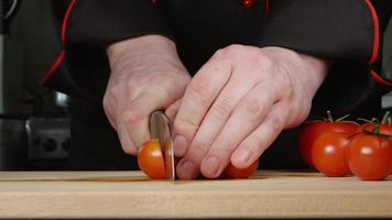A cook cuts a cherry tomatoes on a cutting board in a kitchen