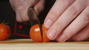 CLOSE UP: A cook cuts a cherry tomatoes on a cutting board in a kitchen