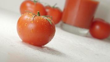 Ein Tropfen fließt von einer reifen Tomate herab. frischer Saft auf einem Hintergrund