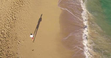 4k Luftaufnahme des jungen fitten athletischen Mannes, der am Strand läuft