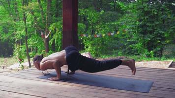 l'homme effectue des exercices de yoga, soulevant une jambe et pliant l'autre