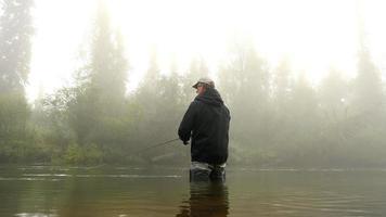 uomo pesca a mosca in un fiume avvolto dalla nebbia