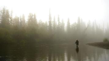 Man Fly-Fishing in a River Enveloped  by Fog