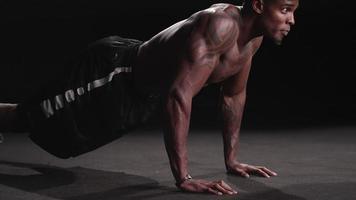 Hombre negro musculoso realizando flexiones militares