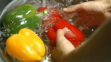 Männerhände waschen Paprika.