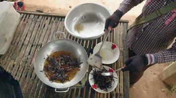 las tarántulas se sumergen en aceite hirviendo para cocinar