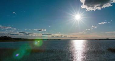 lapso de tempo do sol em forma de estrela descendo sobre um lago video