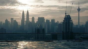 Zeitrafferansicht des Schwimmbades auf dem Wolkenkratzerdach gegen Sonnenaufgang, der Stadtbild errichtet. Kuala Lumpur, Malaysia