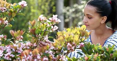 niña bonita mirando flores