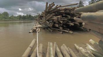 vista ravvicinata del livello dell'acqua sulla pila di pali di bambù immagazzinati in acqua lungo la riva del fiume
