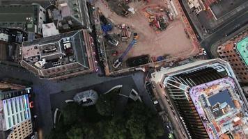 Volando sobre un sitio de construcción y grúas en la ciudad urbana con edificios