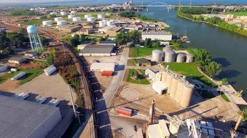 Tren de carbón rodando por el parque industrial sobre el río, vista aérea
