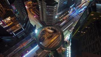 incrocio di traffico leggero di notte con lasso di tempo di strada rotonda 4K dal tetto di hong kong