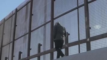 homem anda casualmente ao longo da cerca da fronteira dos EUA e do México