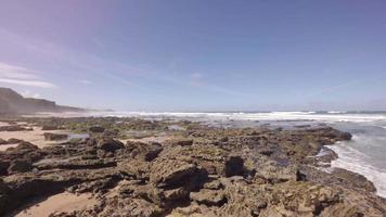 vista aérea de ondas quebrando em uma costa rochosa - praia de santa cruz, torres vedras, portugal video