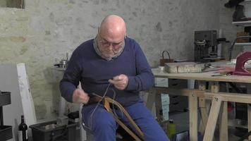 leather goods master craftsman at work video