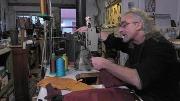 Artesano de artículos de cuero en el trabajo en su taller.