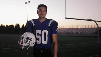 Portrait of a football player on a field holding his helmet video