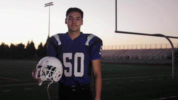 ritratto di un giocatore di football su un campo che tiene il suo casco