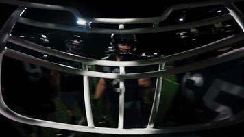 First person point of view from inside a football player's helmet, as the team talks in a huddle
