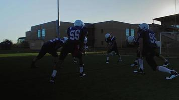 View from outside the circle of football players stretching before a game