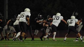 un giocatore di football fatica a superare i suoi avversari e corre verso la end zone