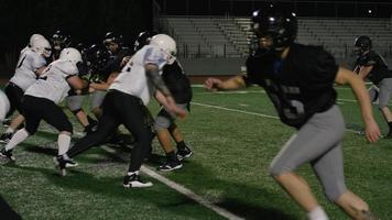 een voetballer duwt tegenstanders neer vlak voordat hij een touchdown maakt
