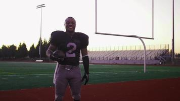 Portrait of a football player on a field catching a football video