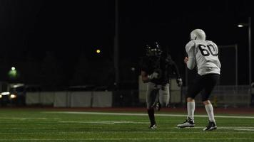 A football player runs hard to catch the football during a game video