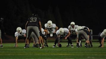 Während eines Spiels wird ein Fußball geschnappt und nachts einem Teamkollegen in Richtung Kamera geworfen