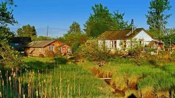 Pântano de pastagem e comunidade de pescadores, casas de aldeia simples