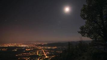 lasso di tempo della vita notturna in città circondata da montagne con la luna